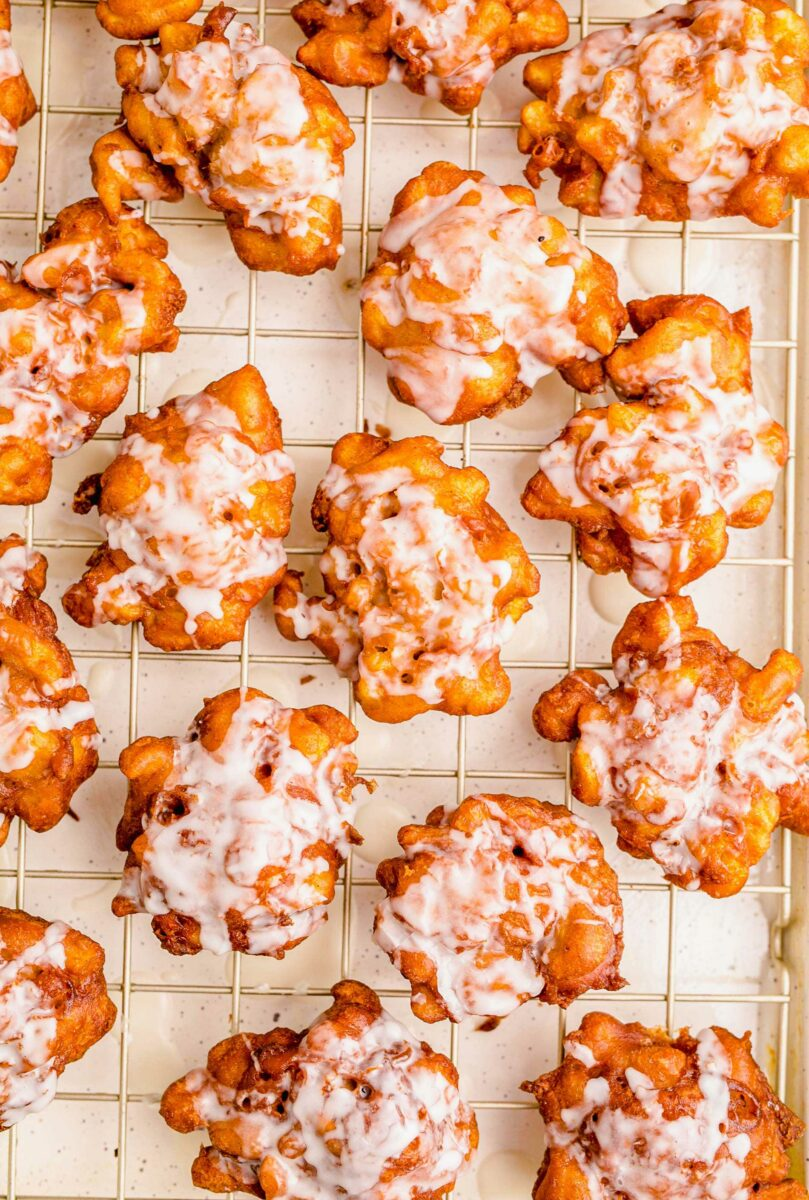 A large batch of apple fritters are spread out on a wire cooling rack that has parchment paper underneath it.