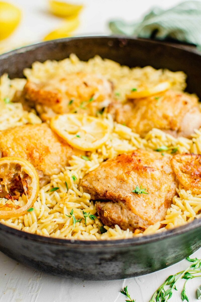 A pan is filled to the brim with cooked orzo, chicken, and lemon slices.