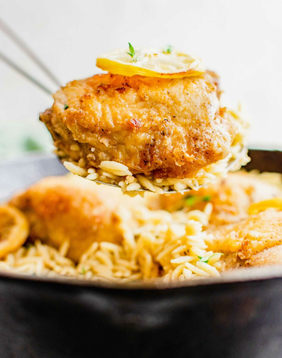 A piece of chicken is being lifted with some orzo from the pan.