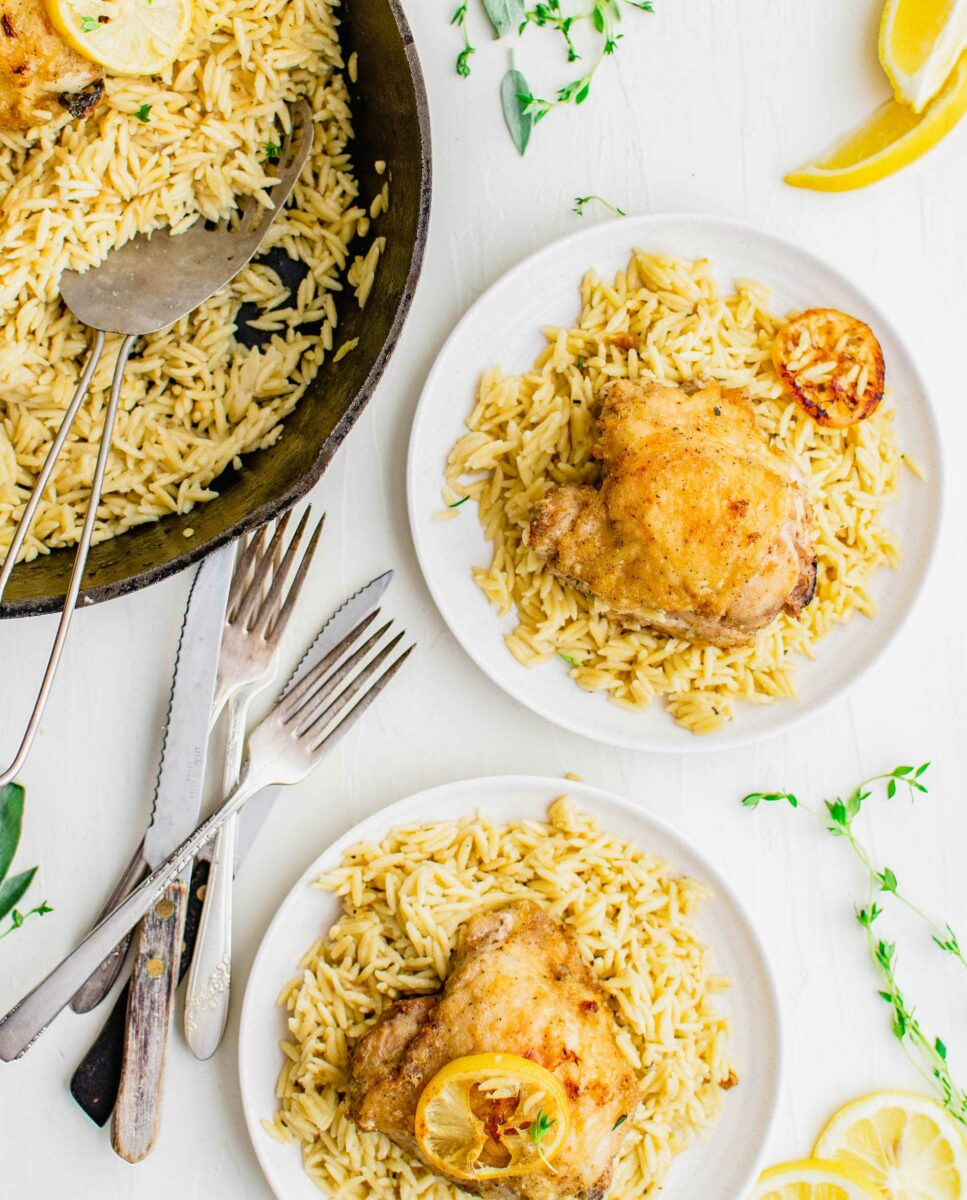Several white plates filled with orzo and chicken are placed next to forks and knives.