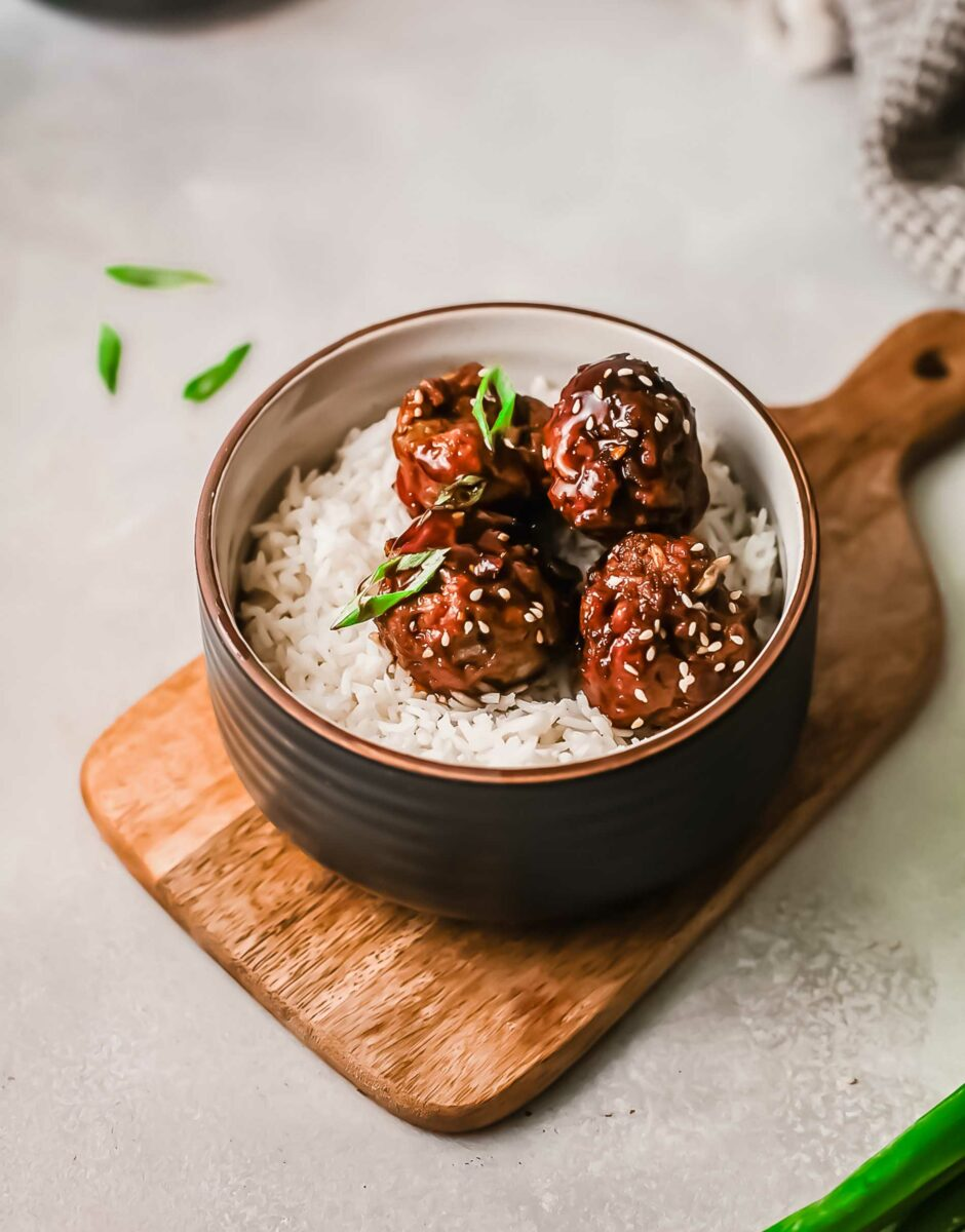 Several meatballs are placed on a bed of white rice.