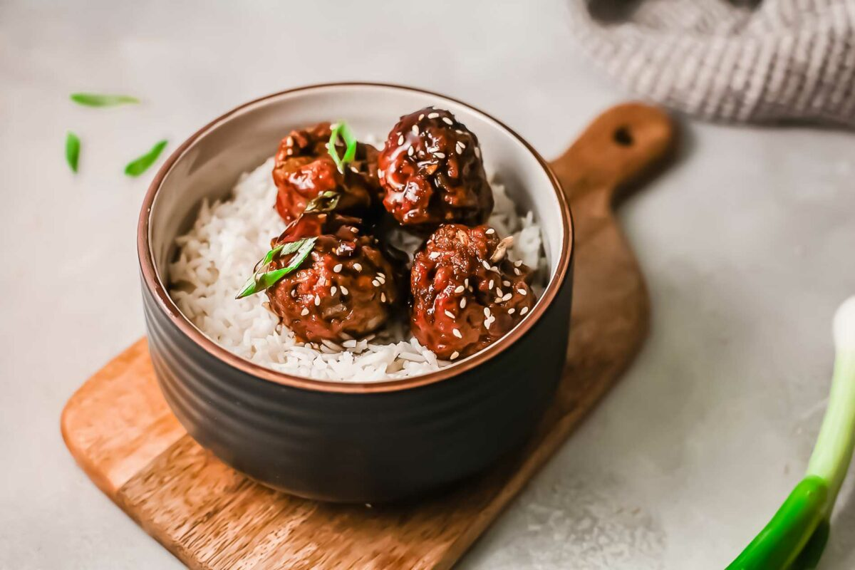Meatballs in white rice in a bowl are placed on a wooden cutting board.