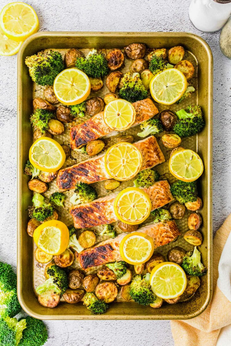 Salmon filets, lemon slices, potatoes and broccoli are spread out on a baking sheet.