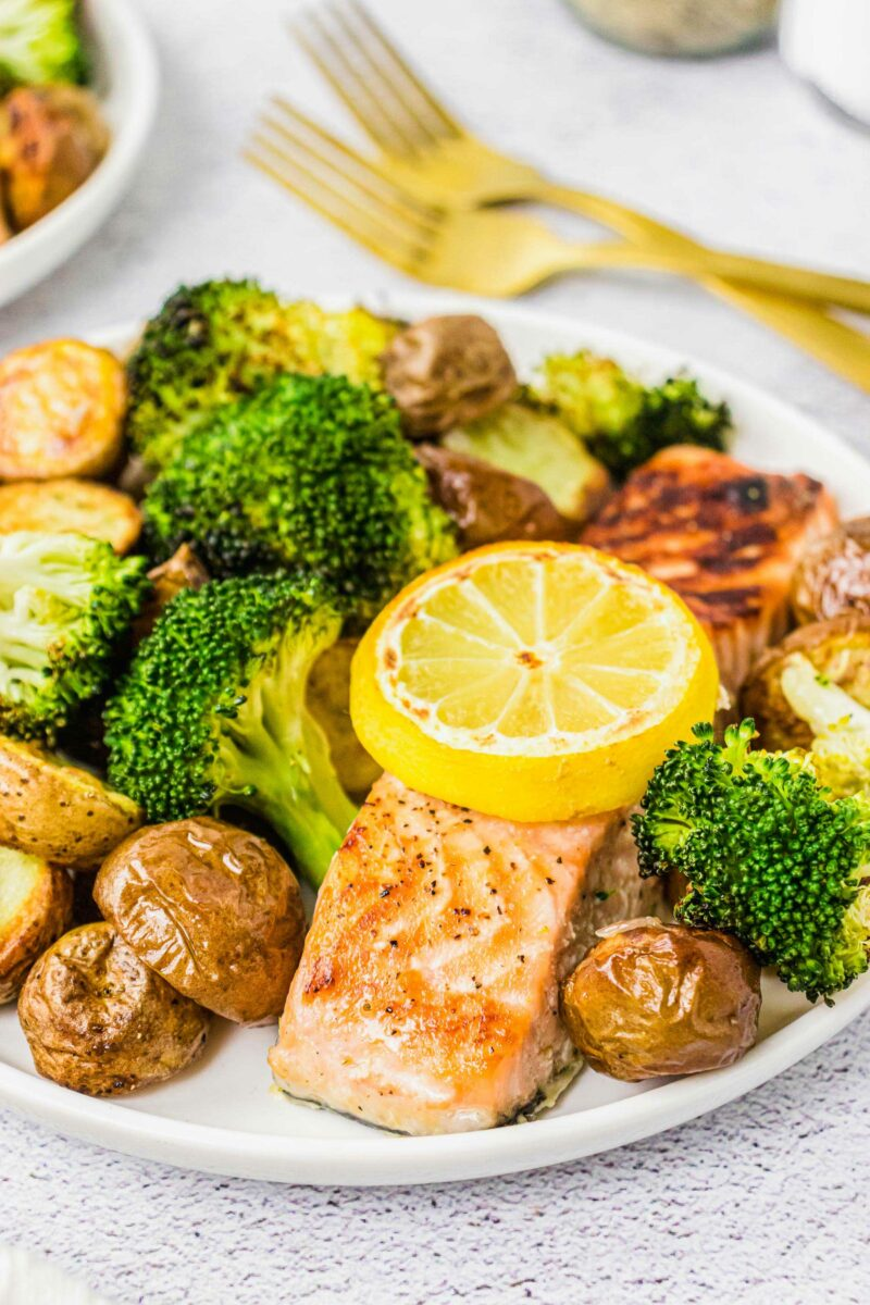 A lemon slice is placed upon a baked salmon filet surrounded by veggies.