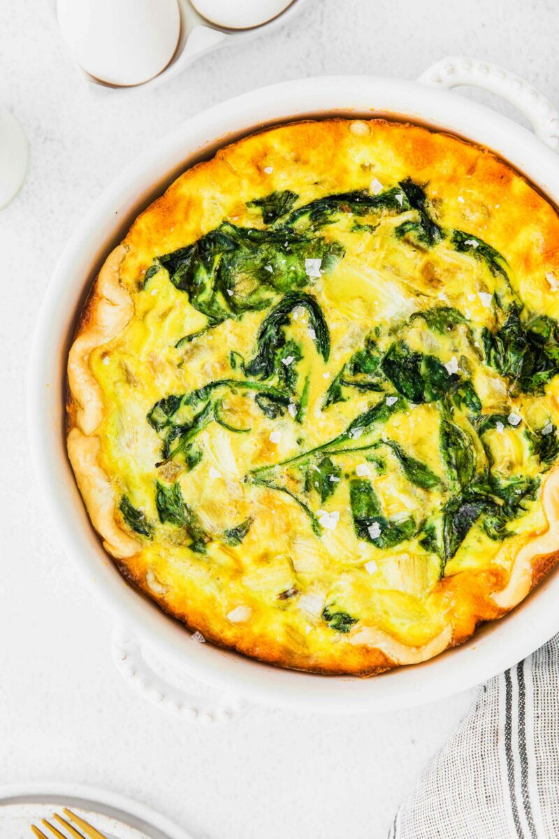 A baked quiche is topped with flaky sea salt.