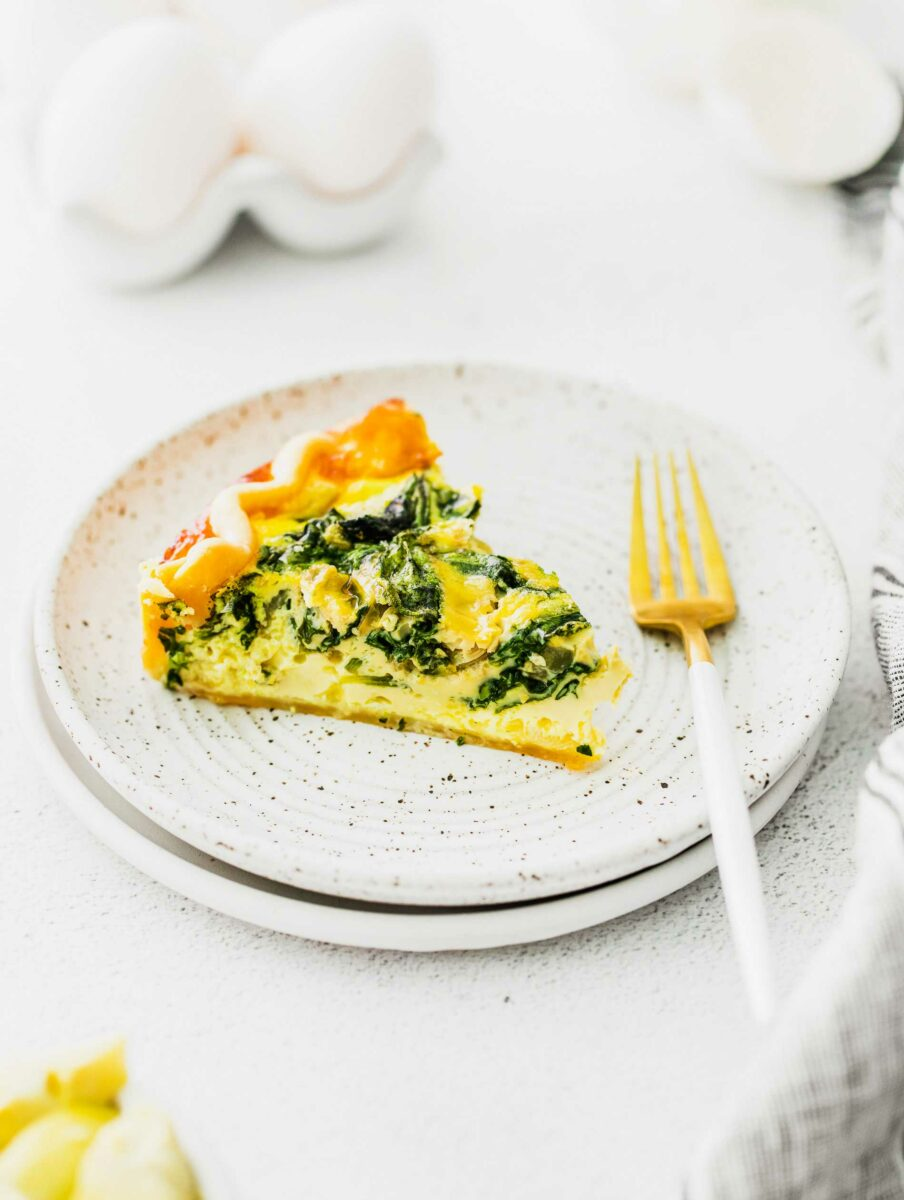 A fork is placed on a white plate that has a single slice of quiche on it.