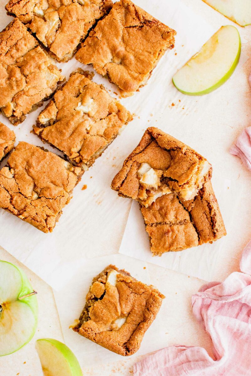 Blondie slices are spread out across parchment paper.