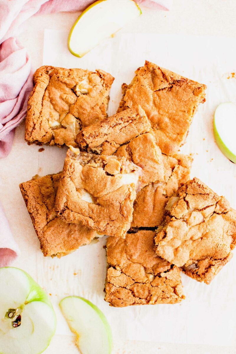 Handheld squares of apple blondies are placed on a white surface next to green apple slices.