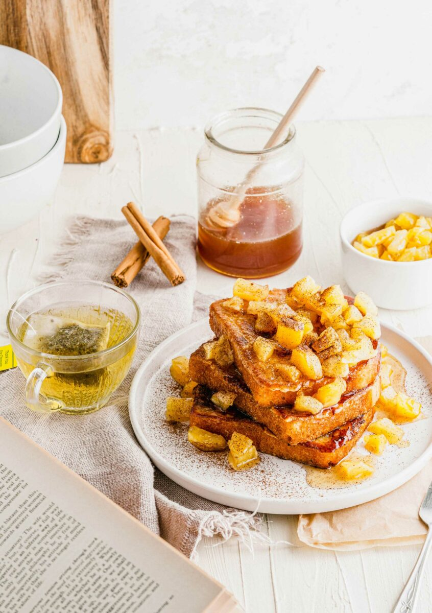 A stack of French toast is topped with caramelized apples.