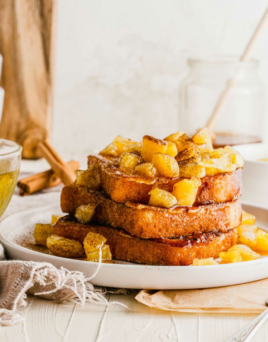 Three pieces of French toast are topped with apples.