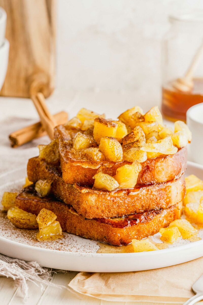 Apples are caramelized, topped with cinnamon, and placed on a stack of French toast.