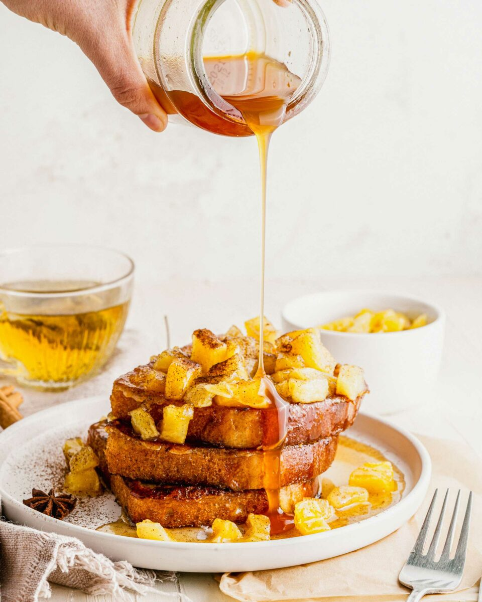 Syrup is being drizzled on top of the French toast and apples.