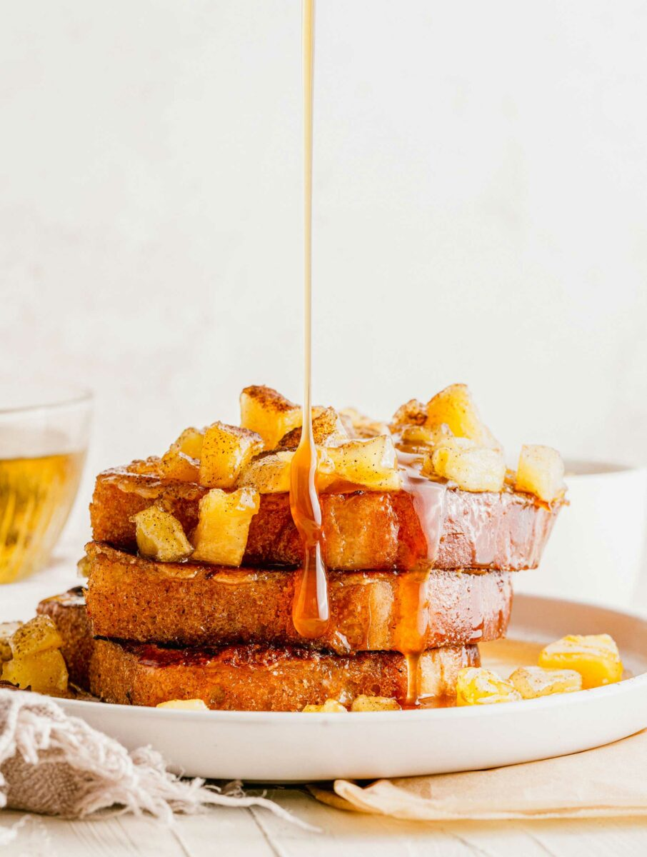 A white plate is stacked with French toast, apples, and syrup.