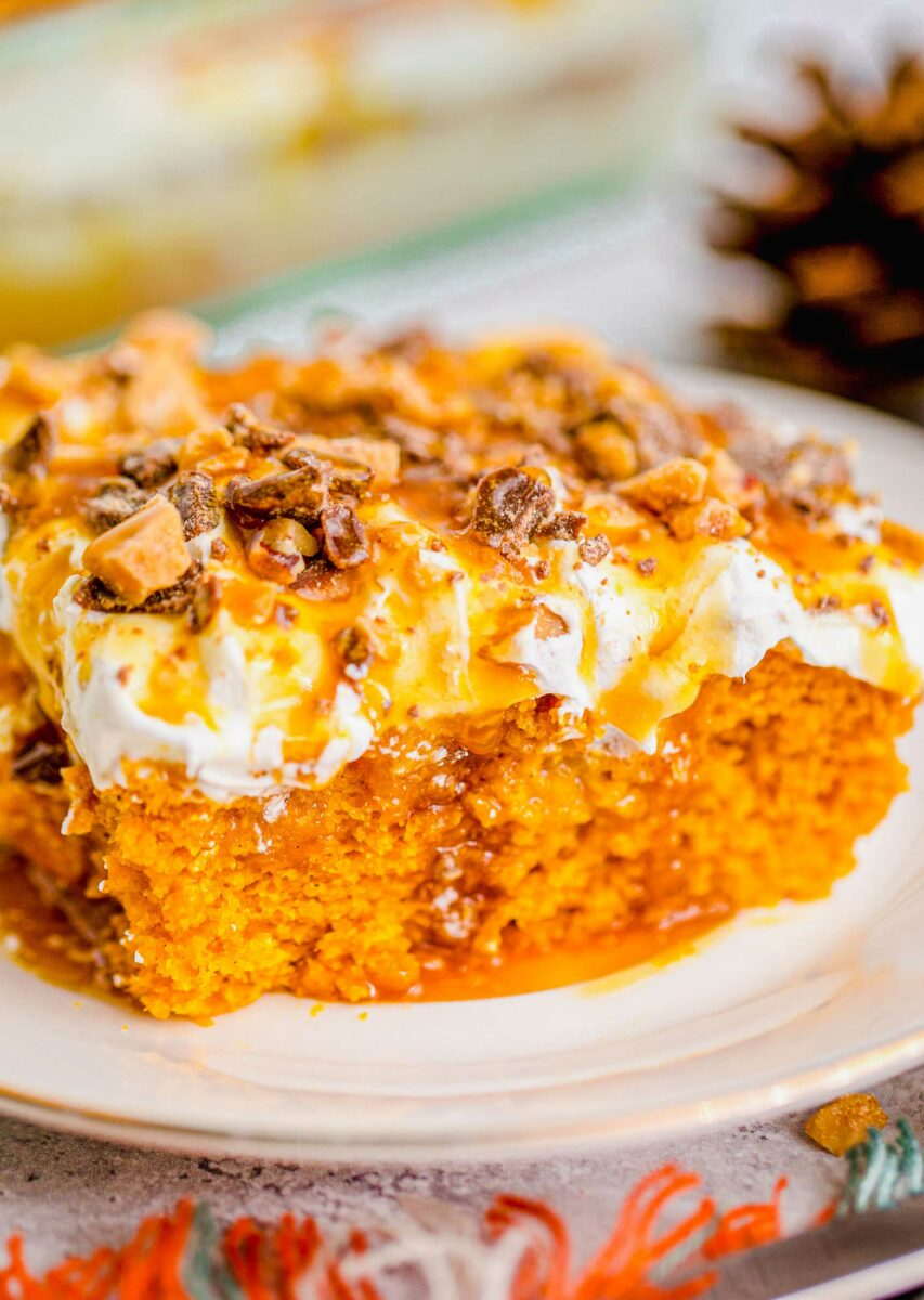 Caramel sauce and toffee bits are covering a slice of pumpkin lush cake.