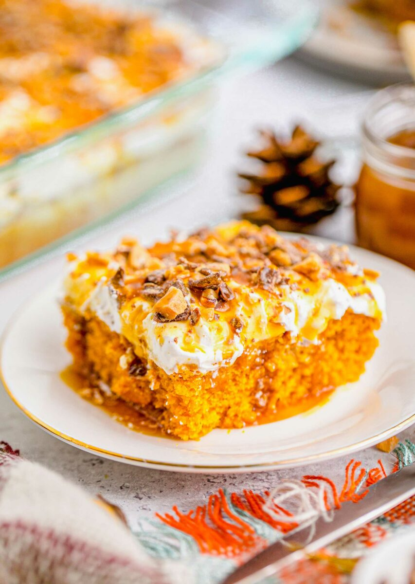 Pumpkin lush cake is drizzled with a hearty amount of caramel sauce.