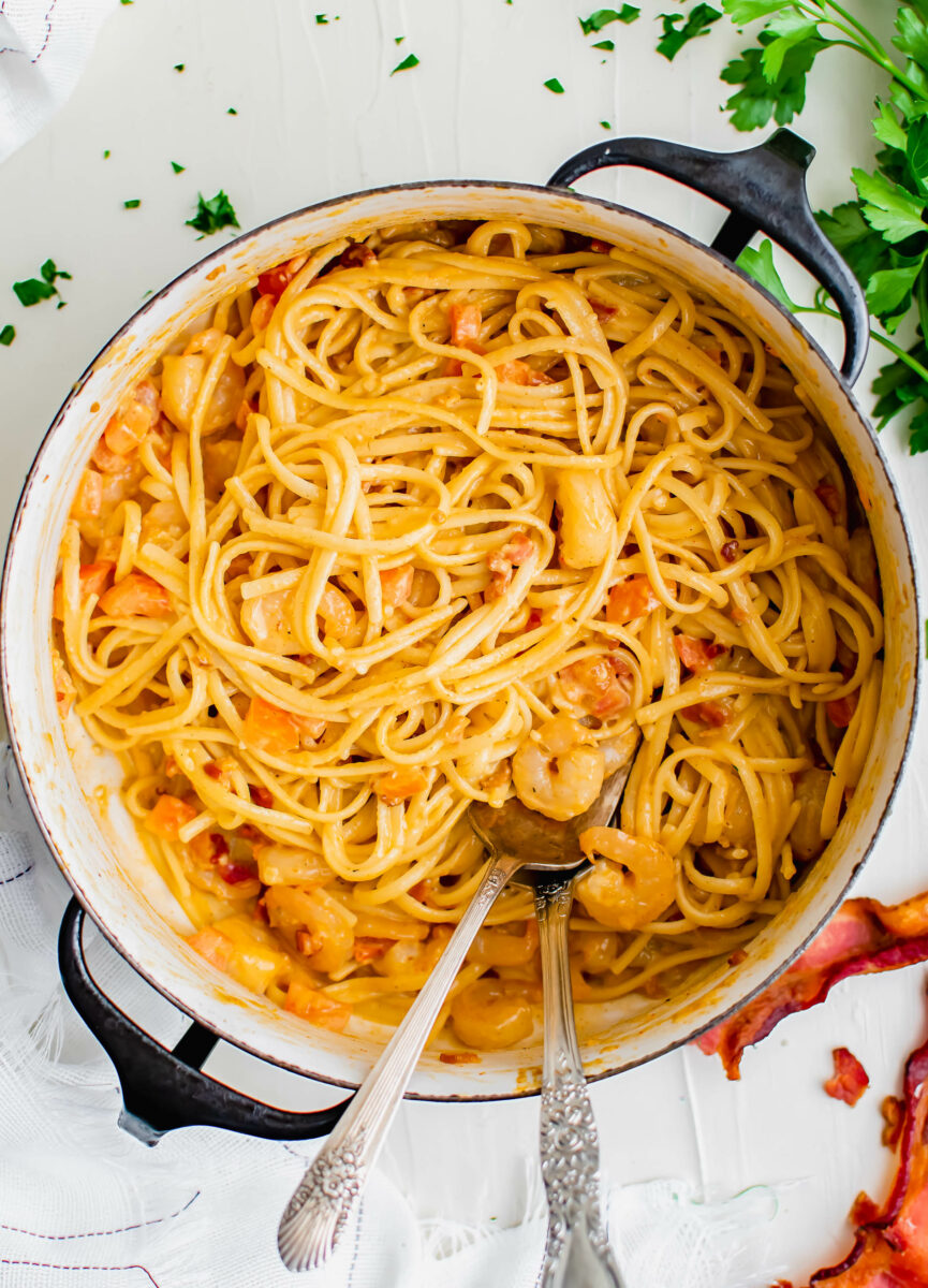 Two spoons are placed in a large pot filled with creamy shrimp pasta.