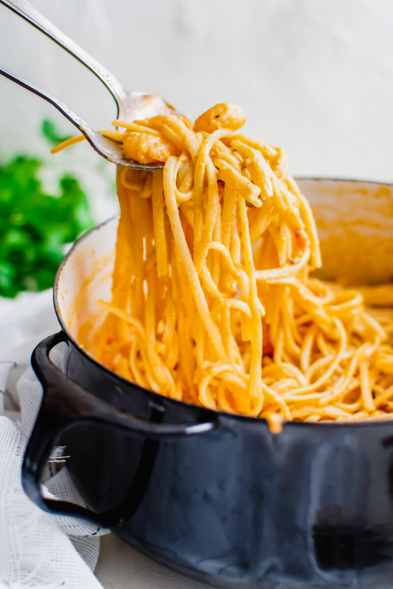 A large black pot is filled with pasta that's being removed from the pot.