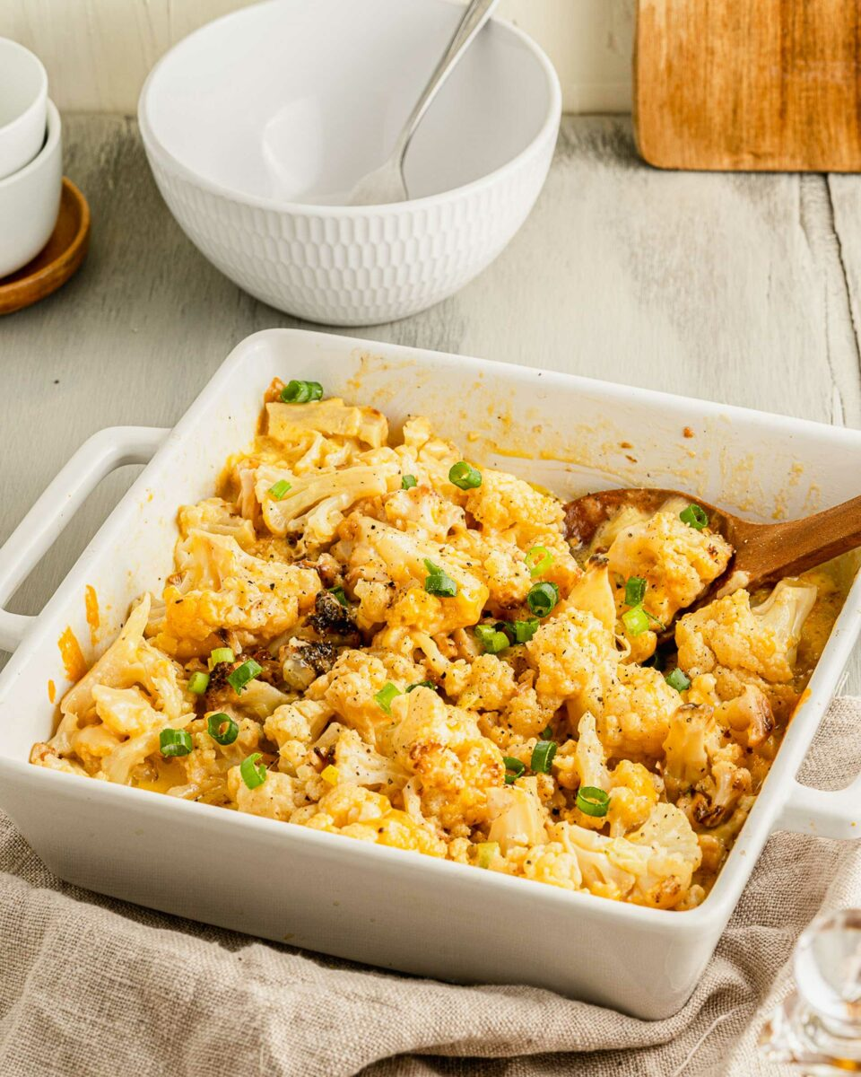 A wooden spoon is placed in a white square casserole dish filled with baked cauliflower and cheese.