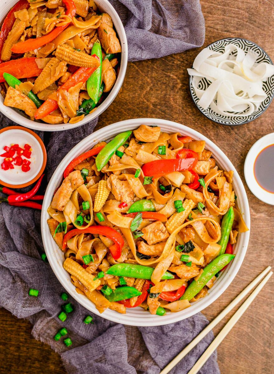 Chopsticks are placed next to a bowl of drunken noodles with chicken.