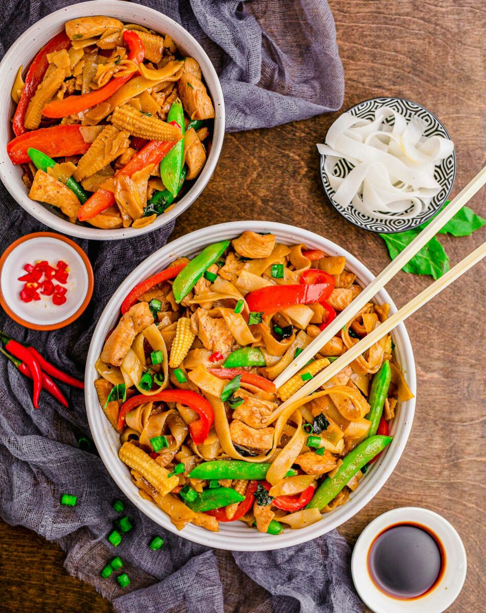A white bowl is filled with noodles, veggies, and chopsticks.