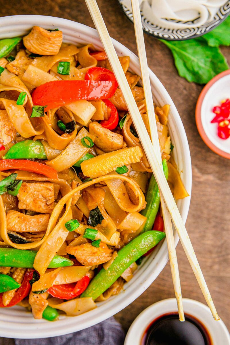 Chopsticks are placed on top of a bowl filled with noodles, chicken and veggies.