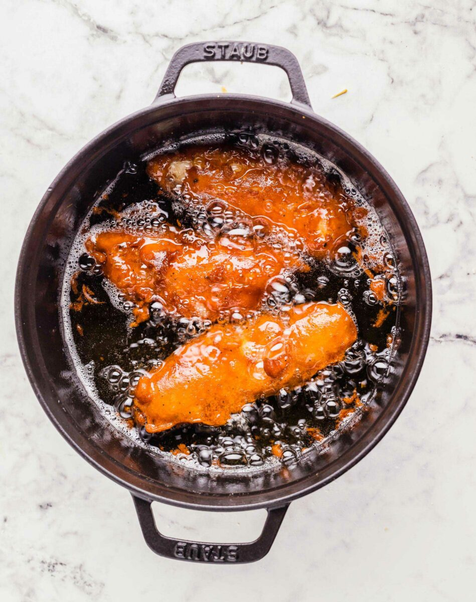 Three pieces of fish are frying in a large black pot.