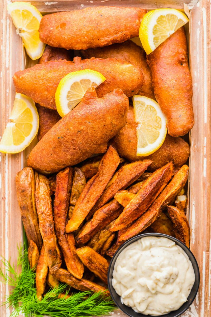 Fried fish is served with lemon slices and fries with a side of tartar sauce.