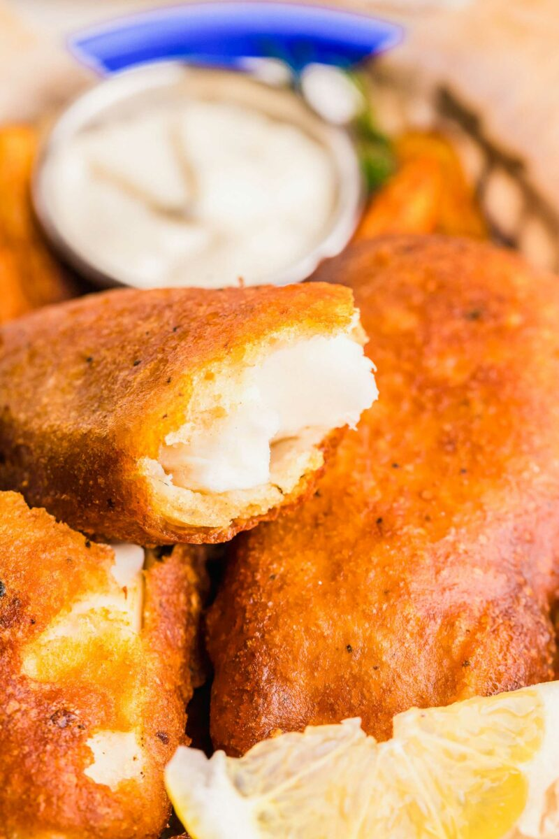 A piece of fish has been split to reveal a perfectly cooked white center and is placed on top of other pieces of fried fish.
