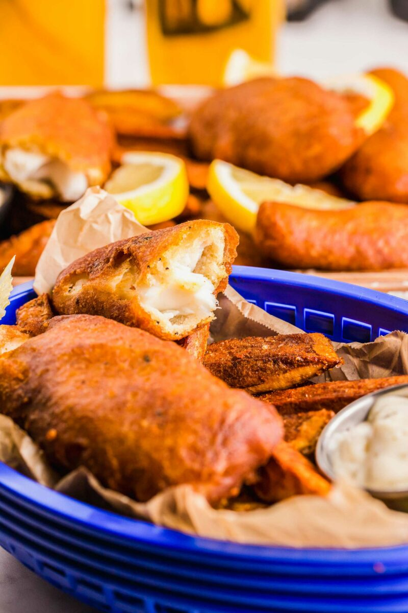 A blue basket is filled with fried fish and chips.