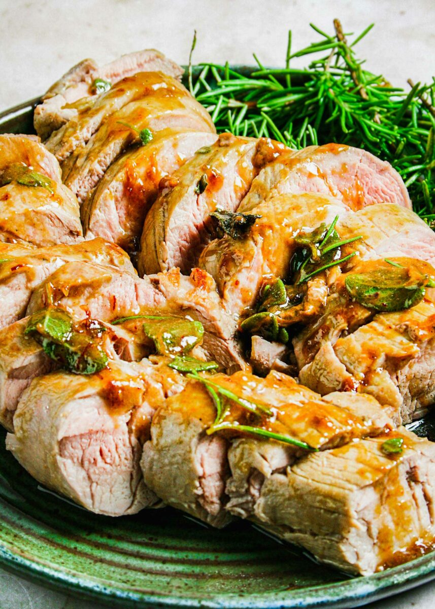 A sliced pork tenderloin is topped with fresh herbs and glaze.