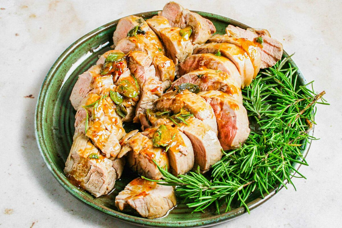 Sliced pork is on a green plate with fresh rosemary sprigs.