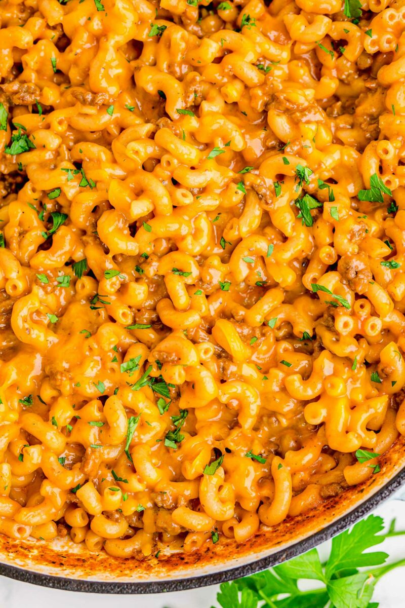 Cheesy noodles and ground beef are garnished with fresh parsley.