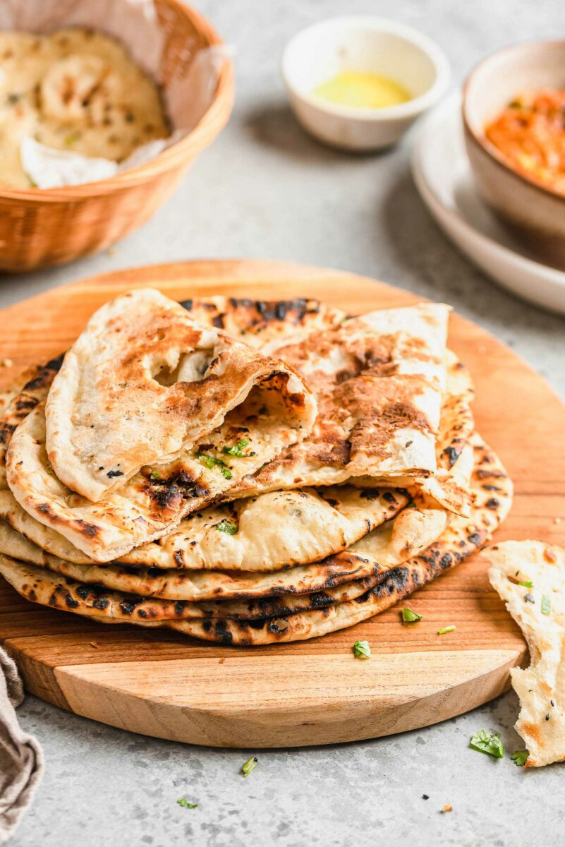 Round pieces of naan are in a stack on a wooden surface.