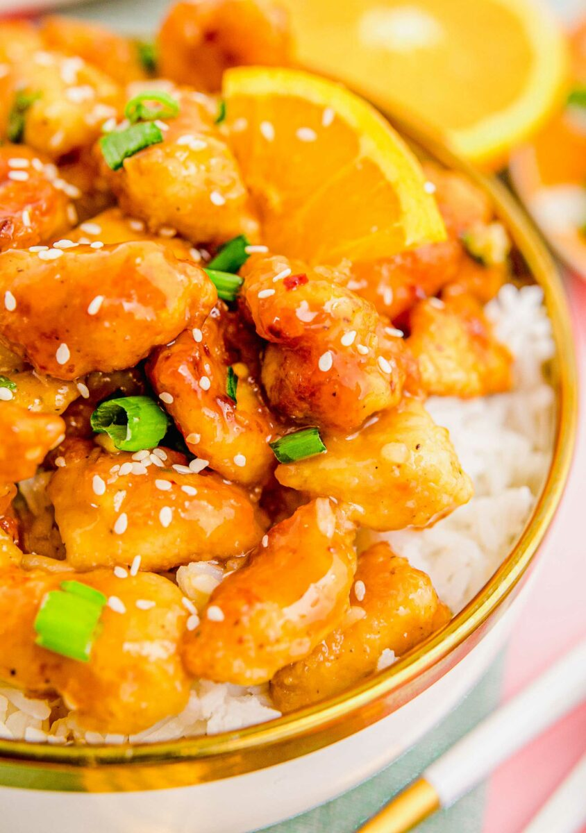 Sesame seeds and scallions sit atop glazed orange chicken in a bowl.