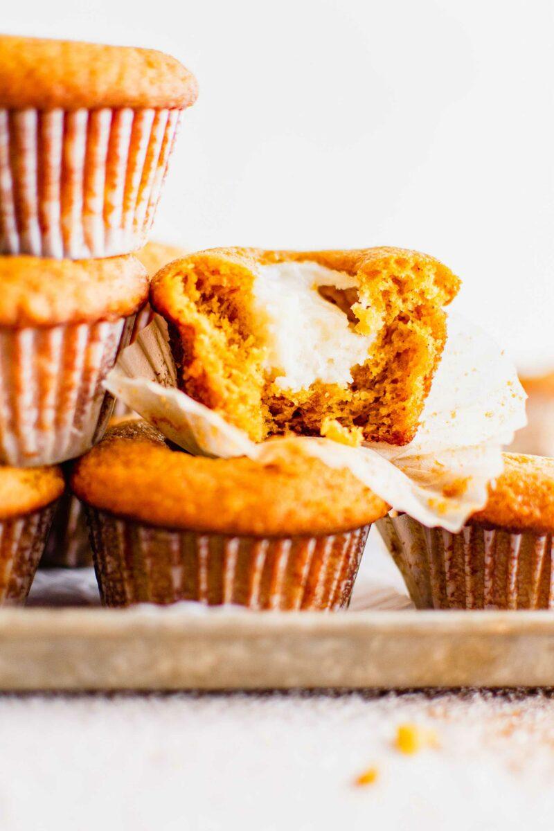 A pumpkin muffin is cut in half, revealing a white cream cheese center.
