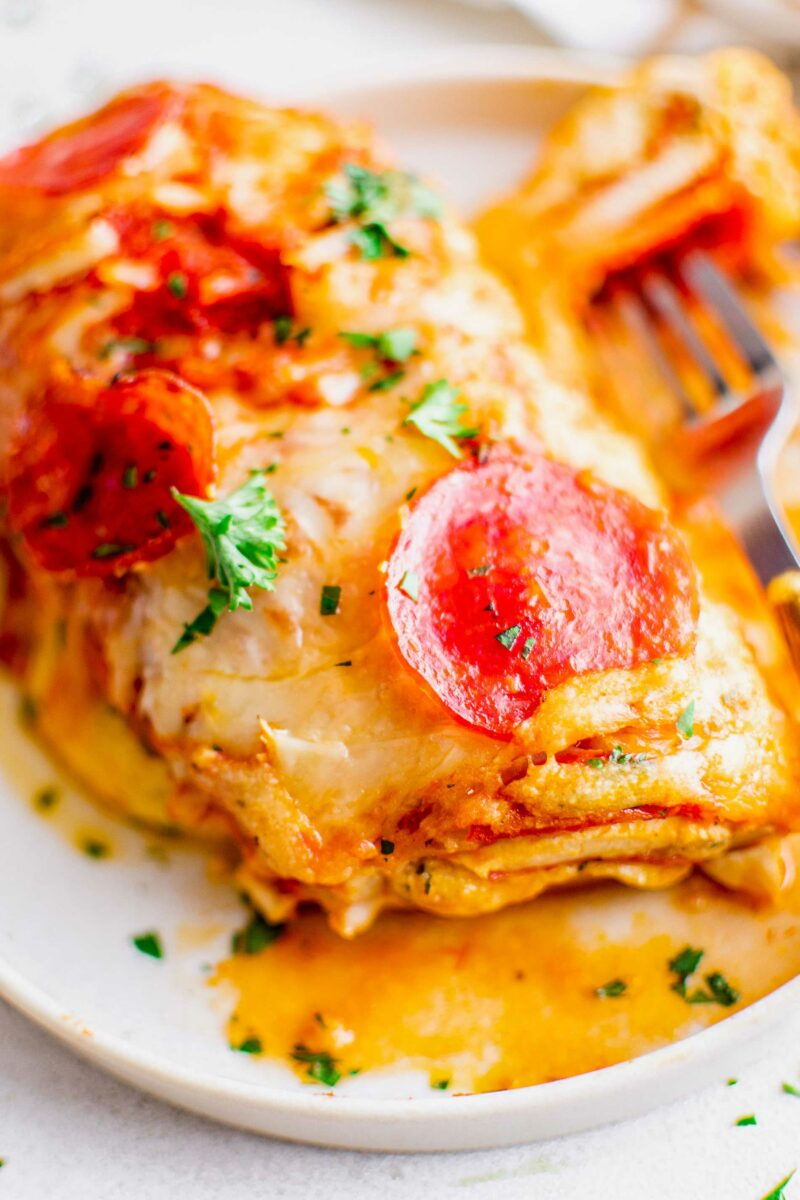 A piece of chicken is fully cooked with pepperoni, cheese, and parsley on top.