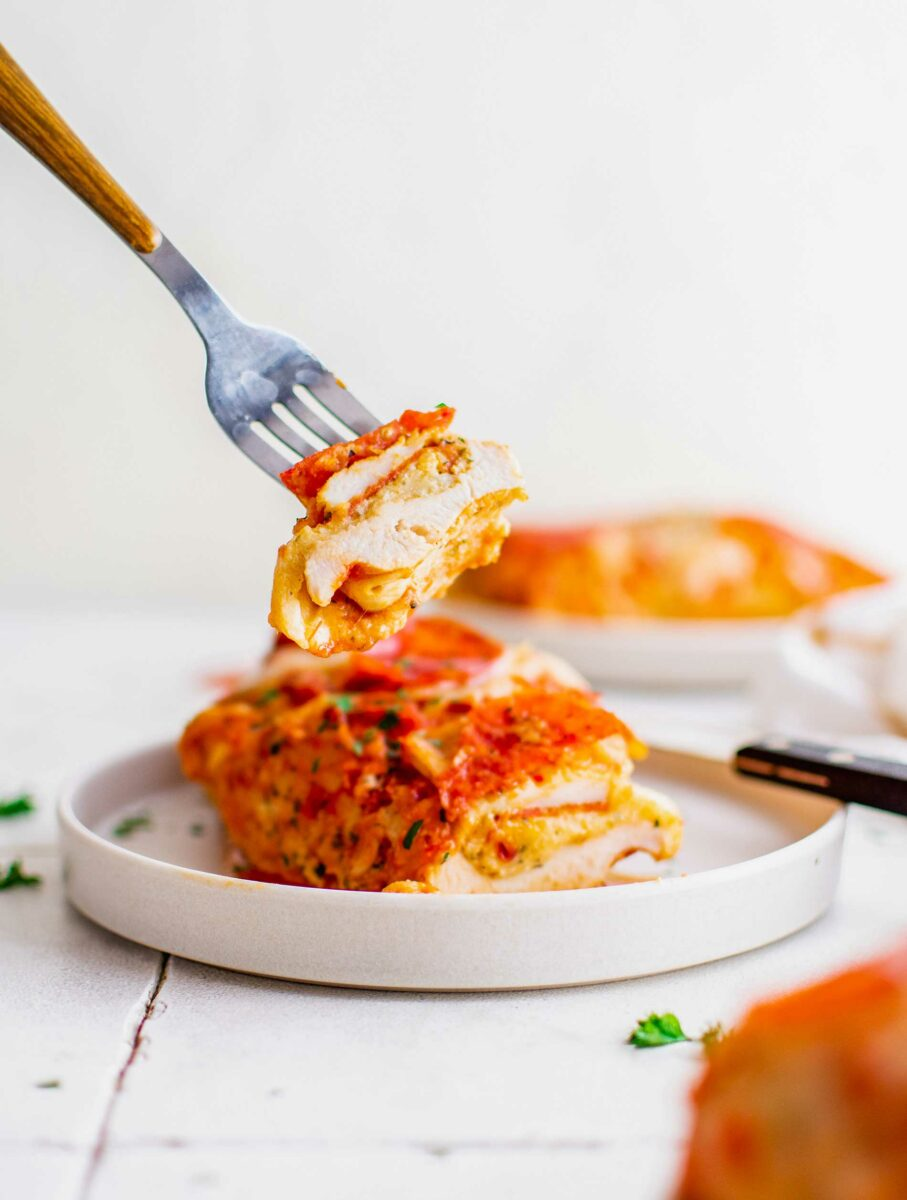 A bite of pizza stuffed chicken is being lifted from a white plate.