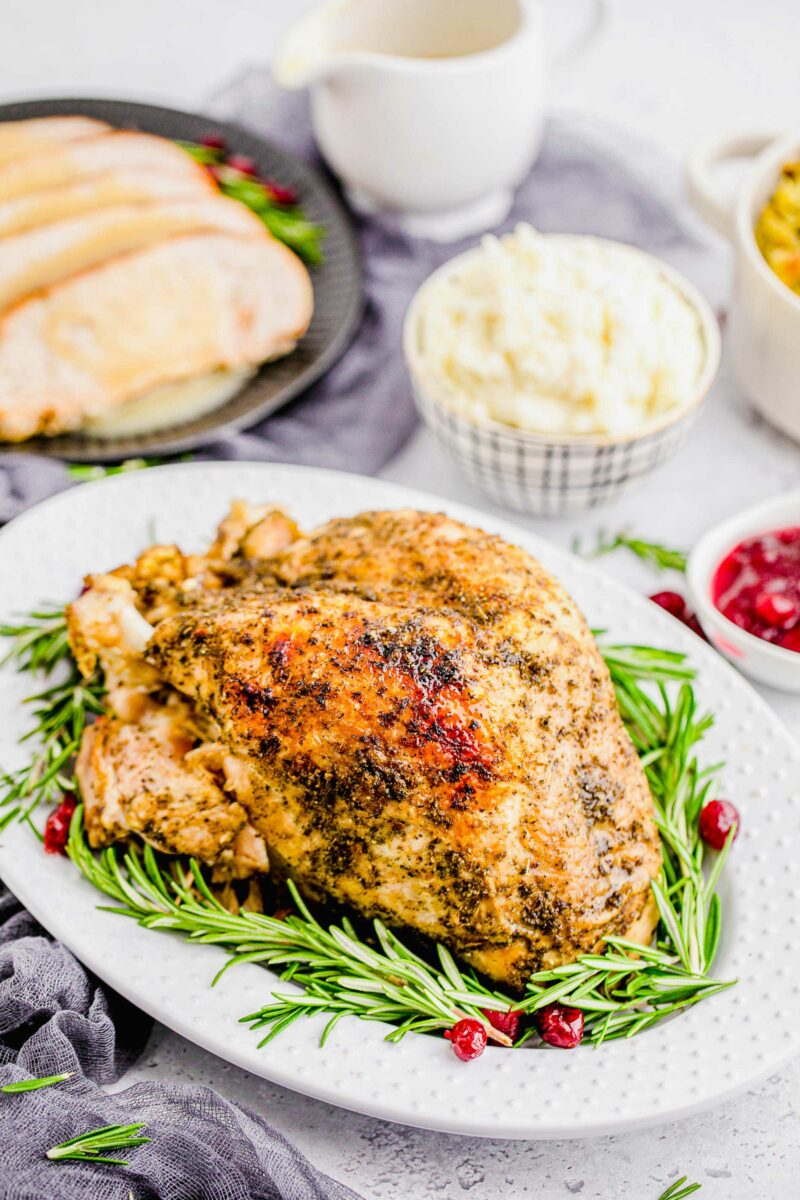Fresh rosemary and candied cranberries are placed around a roasted turkey breast.