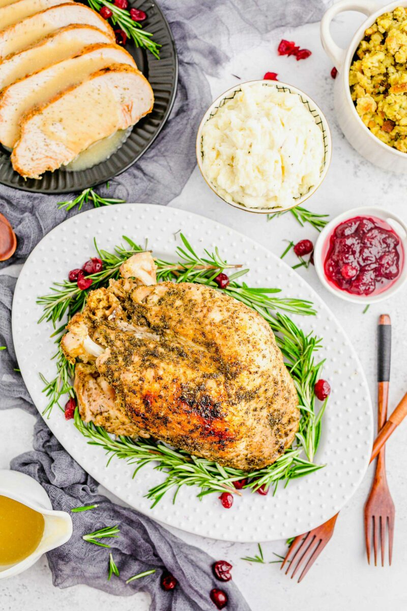 Roasted turkey is surrounded by cranberry sauce, mashed potatoes, stuffing, and flatwarre.