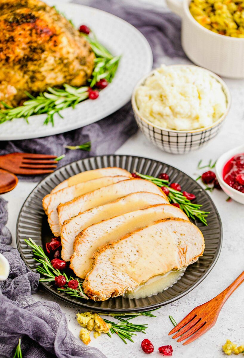 Sliced turkey breast is presented on a black plate with gravy, rosemary, and cranberries.