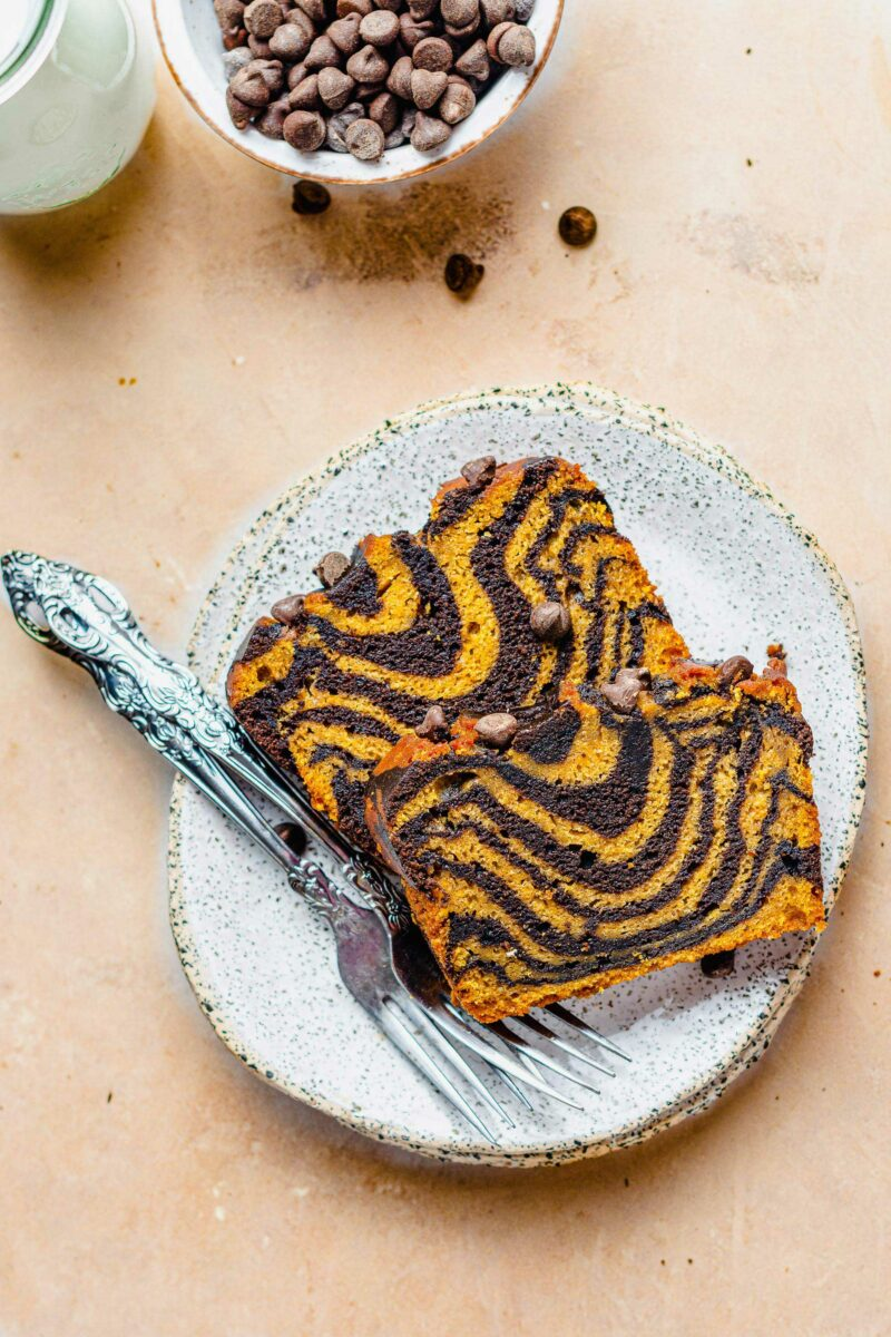 Two forks are placed next to two pieces of pumpkin chocolate bread.